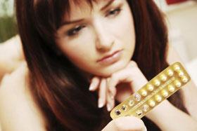 Femme dubitative face à sa plaquette de pilules